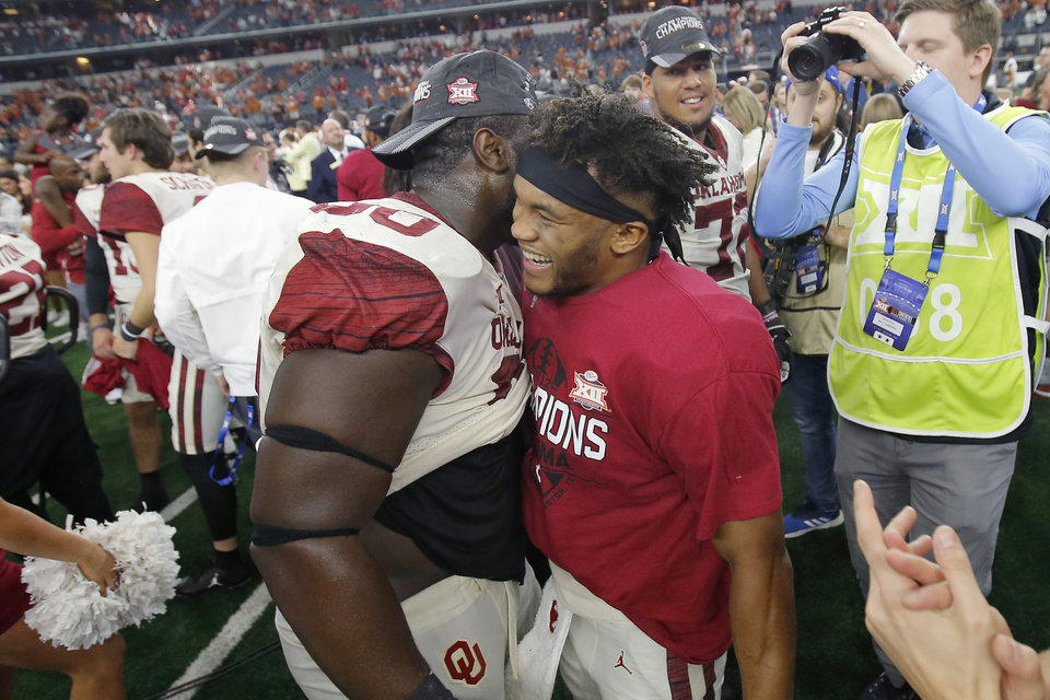 Photo - Oklahoma's Kyler Murray celebrates with Neville Gallimore (90) after the Big 12 Championship football game between the Oklahoma Sooners (OU) and the Texas Longhorns (UT) at AT&T Stadium in Arlington, Texas, Saturday, Dec. 1, 2018.  Oklahoma won 39-27. Photo by Bryan Terry, The Oklahoman
