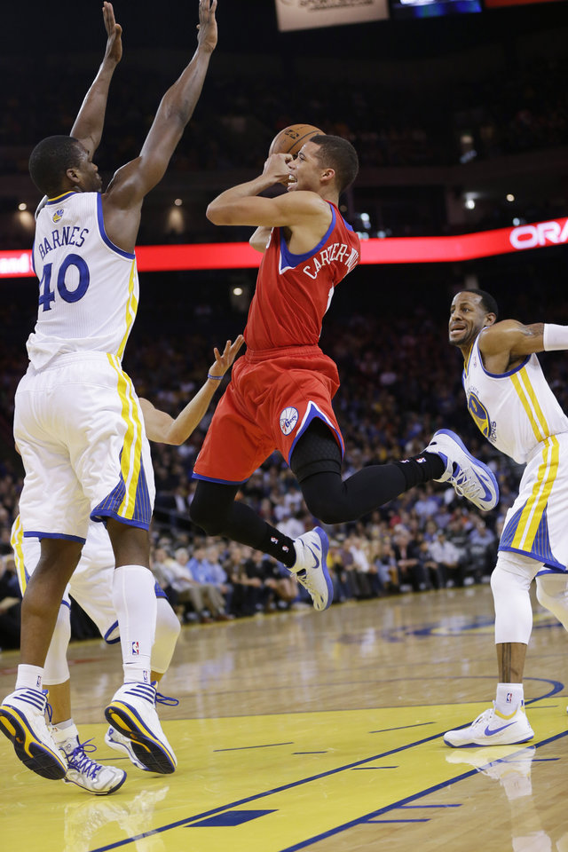 Photo - Philadelphia 76ers' Michael Carter-Williams, center, shoots between, Golden State Warriors' Harrison Barnes (40) and Andre Iguodala (9), right, during the first half of an NBA basketball game, Monday, Feb. 10, 2014, in Oakland, Calif. (AP Photo/Marcio Jose Sanchez)