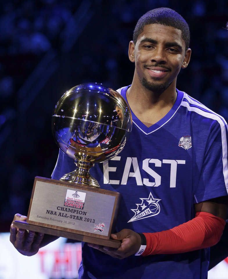 Kyrie Irving of the Cleveland Cavaliers holds the trophy after winning the 3-point contest during NBA basketball All-Star Saturday Night, Feb. 16, 2013, in Houston. (AP Photo/Eric Gay)