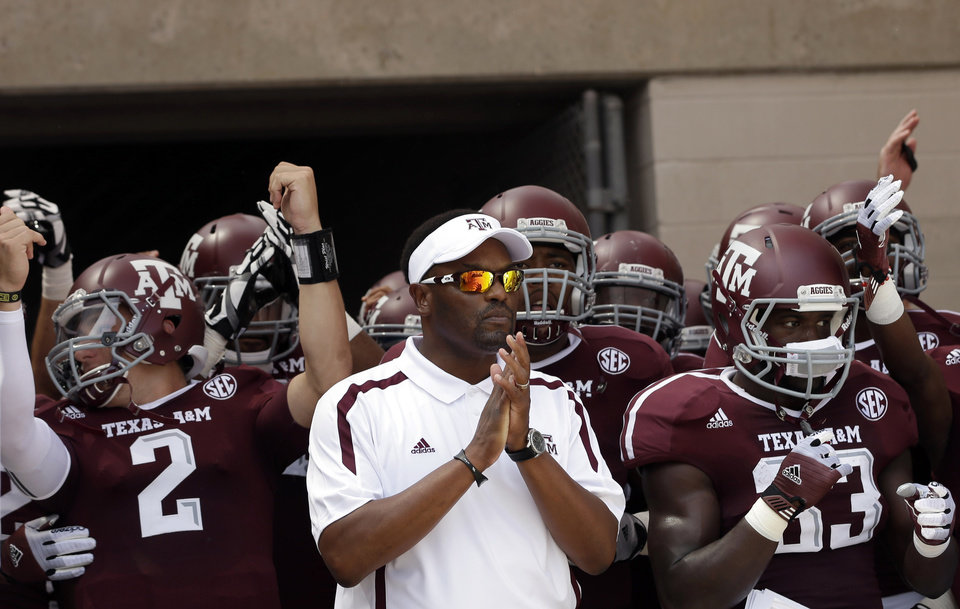 Photo -   FILE - In this Sept. 8, 2012, file photo, Texas A&M coach Kevin Sumlin, center, prepares to lead his team onto the field for an NCAA college football game against Florida in College Station, Texas. Texas A&M begins a stretch of three straight road games on Saturday when the 22nd-ranked Aggies visit Auburn. They aren't concerned about the tough road stretch. The first-year A&M coach has won his nine straight games away from home dating back to his time at Houston. (AP Photo/David J. Phillip, File)