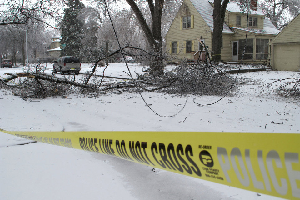 Photo - Downed power lines are cordoned off with police tape near Phillips Avenue on Wednesday, April 10, 2013, in Sioux Falls, S.D. A spring storm that began Tuesday and was expected to last through Thursday wreaked havoc on roads, downed branches and knocked out power for thousands of residents. (AP Photo/Amber Hunt)