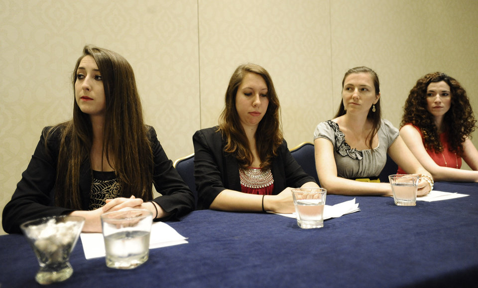 Photo - From left, University of Connecticut students Carolyn Luby, Erica Daniels, Kylie Angell, and Rosemary Richi listen as attorney Gloria Allred, addresses the media during a news conference, Friday, July 18, 2014, in Hartford, Conn.  The University of Connecticut will pay nearly $1.3 million to settle a federal lawsuit filed by five women who claimed the school responded to their sexual assault complaints with indifference, the two sides announced Friday.  (AP Photo/Jessica Hill)