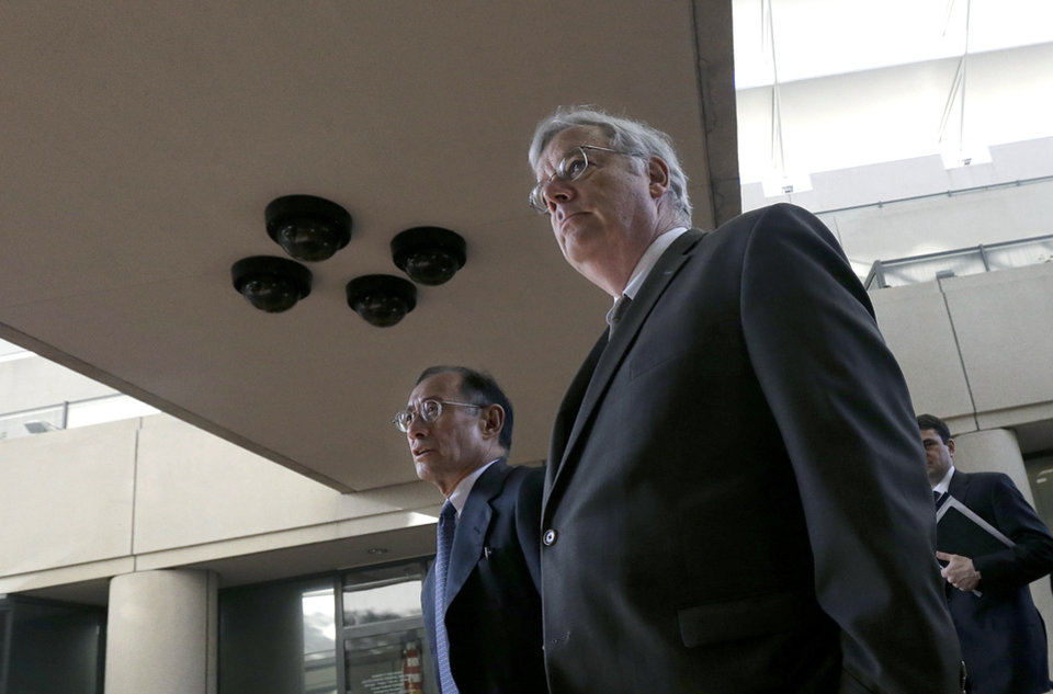 Photo - Apple attorneys Harold McElhinny, foreground, and William Lee walk to a federal courthouse in San Jose, Calif., Tuesday, April 29, 2014. The Silicon Valley court battle between Apple and Samsung is entering its final phase. Lawyers for both companies are expected to deliver closing arguments Tuesday before jurors are sent behind closed doors to determine a verdict in a closely watched trial over the ownership of smartphone technology. (AP Photo/Jeff Chiu)