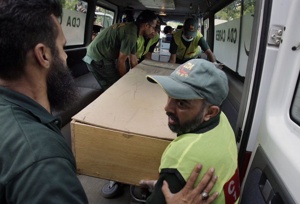 Photo - Pakistani rescue workers unload the casket of a foreign tourist, who was killed by Islamic militants, from an ambulance to shift in a morgue of local hospital in Islamabad, Pakistan, Sunday, June 23, 2013. Islamic militants wearing police uniforms shot to death nine foreign tourists and one Pakistani before dawn as they were visiting one of the world's highest mountains in a remote area of northern Pakistan that has been largely peaceful, officials said. (AP Photo/Anjum Naveed)