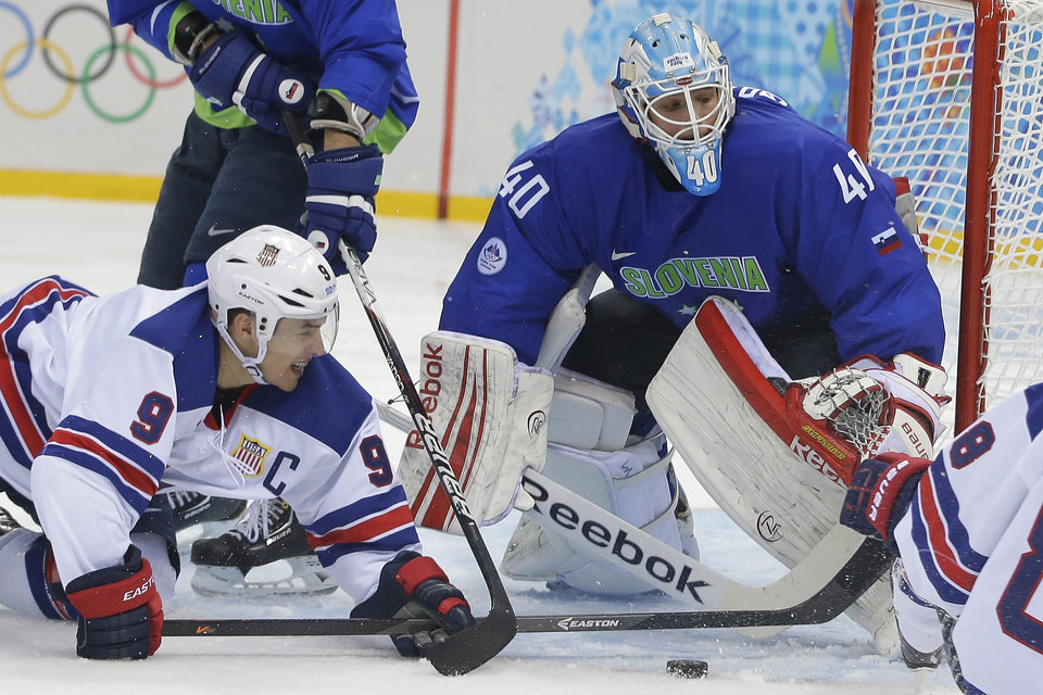 Photo - USA forward Zach Parise reaches for a loose puck in front of Slovenia goaltender Luka Gracnar during the 2014 Winter Olympics men's ice hockey game at Shayba Arena Sunday, Feb. 16, 2014, in Sochi, Russia. (AP Photo/Matt Slocum)