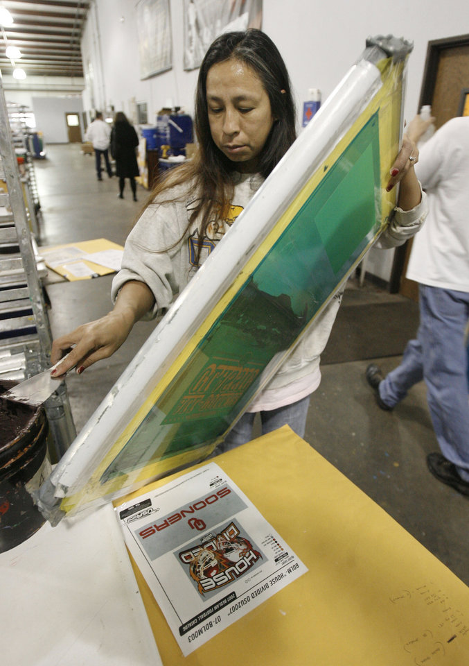 Photo - BIG 12 CHAMPIONSHIP, MERCHANDISE: Edwina Stewart scrapes excess ink off of a screen at USA Screen Printing in Oklahoma City, OK, Thursday, Nov. 29, 2007. By Paul Hellstern / The Oklahoman ORG XMIT: KOD