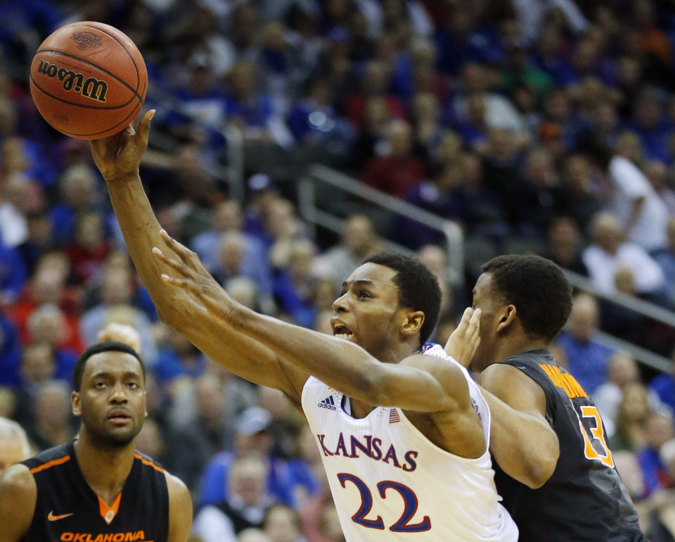 Photo - Kansas guard Andrew Wiggins (22) is fouled by Oklahoma State guard Leyton Hammonds, right,  while shooting during the second half of an NCAA college basketball game in the quarterfinals of the Big 12 Conference men's tournament in Kansas City, Mo., Thursday, March 13, 2014. Kansas defeated Oklahoma State 77-70 in overtime. (AP Photo/Orlin Wagner)