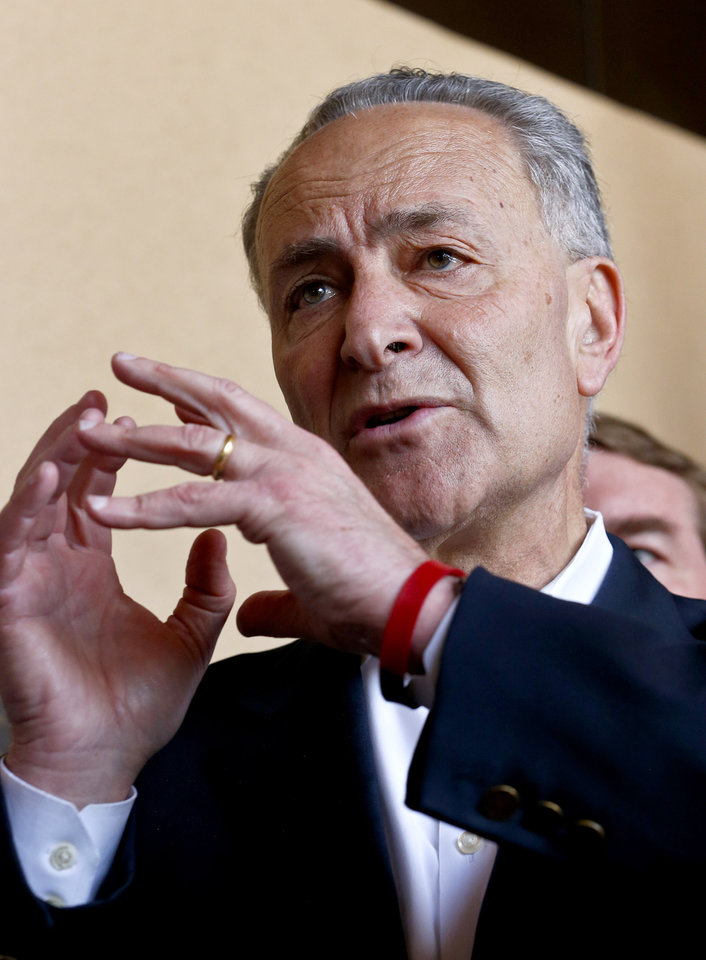 Photo - Sen. Chuck Schumer, D-N.Y., makes a point as he is joined by Sen. John McCain, R-Ariz., Sen. Jeff Flake, R-Ariz., and Sen. Michael Bennett, D-CO, during a news conference after their tour of the Mexico border with the United States on Wednesday, March 27, 2013, in Nogales, Ariz.  A group of influential U.S. senators shaping and negotiating details of an immigration reform package vowed Wednesday to make the legislation public when Congress reconvenes next month. (AP Photo/Ross D. Franklin)