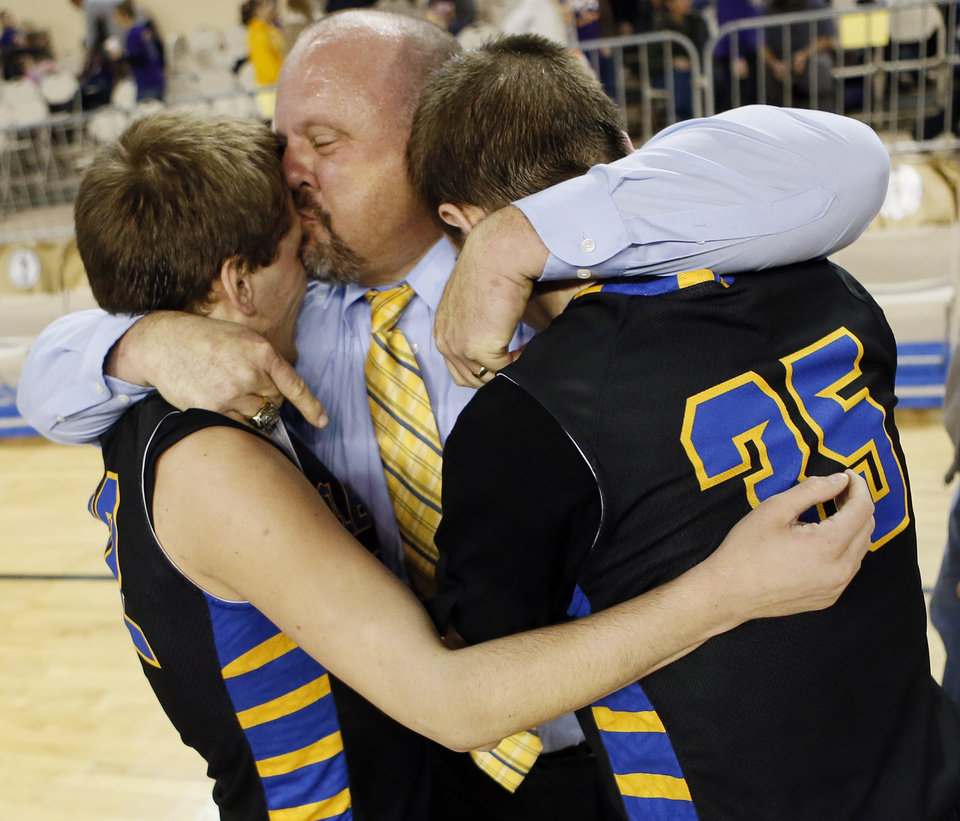 Photo - Glencoe coach John Lazenby hugs his sons Jake Lazenby (22), left, and Ty Lazenby (35) after winning a Class A boys semifinal high school basketball game in the state championship tournament between Weleetka and Glencoe at The Big House, Jim Norick State Fair Arena, in Oklahoma City, Friday, March 7, 2014. Glencoe won, 73-67. Photo by Nate Billings, The Oklahoman