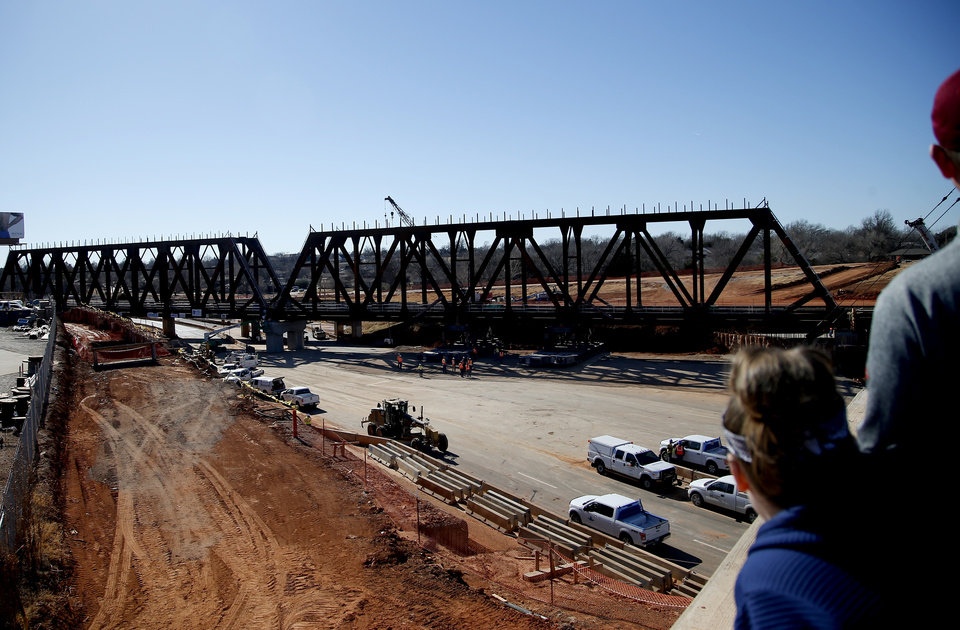 Photo -  People watch from a viewing area Sunday as workers install the new railroad bridge over Interstate 235 in Oklahoma City. [Photo by Sarah Phipps, The Oklahoman]