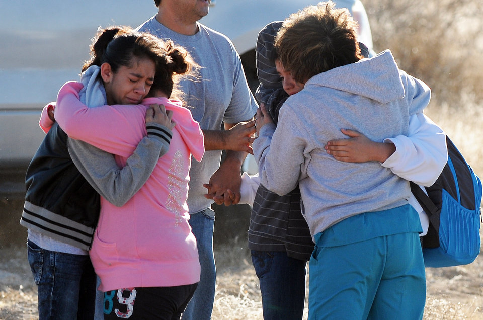 Photo - Students are reunited with family following a shooting at Berrendo Middle School, Tuesday, Jan. 14, 2014, in Roswell, N.M. Roswell police said the suspected shooter was arrested at the school, but authorities have not said if there were any injuries. The school has been placed on lockdown. No other details are yet available. (AP Photo/Roswell Daily Record, Mark Wilson)