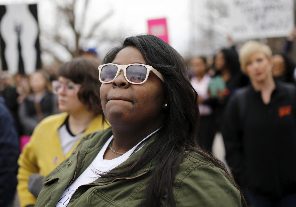 Photo - Brondalyn Coleman, Oklahoma City, listens to one of the speakers. A crowd estimated by organizers to be as many as 7,000 people came to the state Capitol in Oklahoma City Saturday, Jan. 21, 2017, to rally, using their voices and signs to express displeasure with the nation's new administration as part of a larger network of marches taking place across the country following Donald Trump's inauguration.   The Women's March on Oklahoma included a walk along Lincoln Blvd., with the Capitol as a backdrop, and a rally on the Capitol's south plaza that featured nearly a dozen speakers.  Photo by Jim Beckel, The Oklahoman