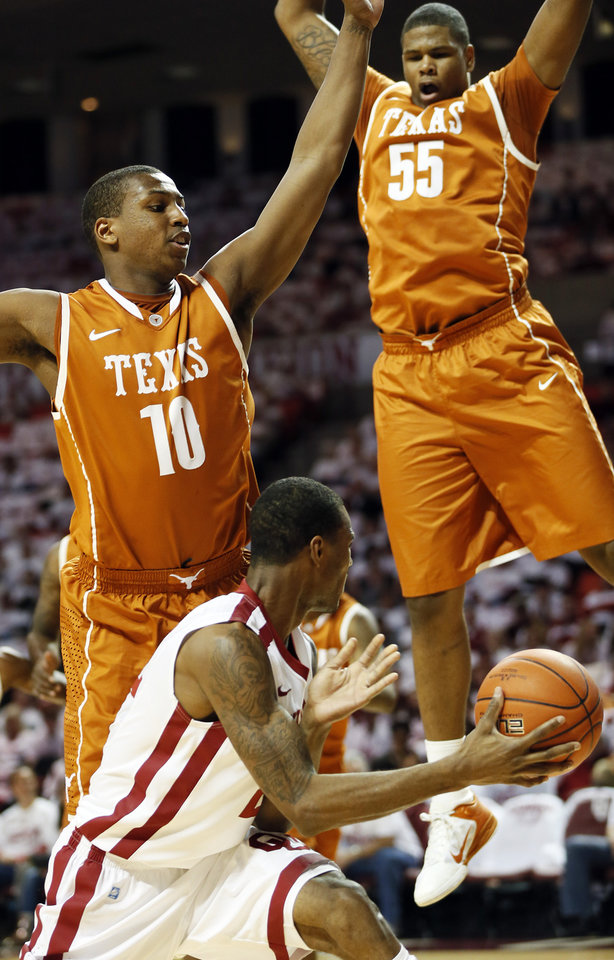 Photo - Oklahoma's Amath M'Baye (22) passes around Texas' Jonathan Holmes (10) and Cameron Ridley (55) during a men's college basketball game between the University of Oklahoma (OU) and the University of Texas at the Lloyd Noble Center in Norman, Okla., Monday, Jan. 21, 2013. Photo by Nate Billings, The Oklahoman