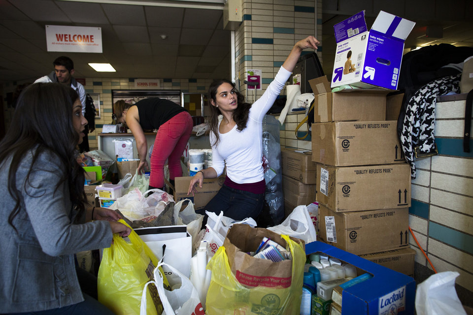 FILE - In this Sunday, Nov. 4, 2012 file photo, volunteer Jamie d'Amico, 25, of Fort Lee, helps sort through donations at Hoboken High School as surrounding neighborhoods remain without power due to damage caused by Superstorm Sandy, in Hoboken, N.J. Donations are rolling into New York and New Jersey after Superstorm Sandy, but some relief experts say the things being given are not always what's needed. (AP Photo/ John Minchillo, File)