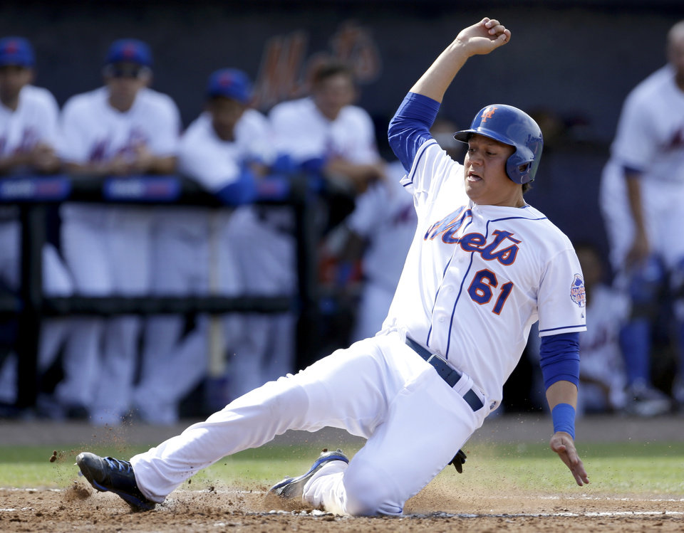 Photo - New York Mets' Wilmer Flores scores on a hit by Justin Turner and a throwing error by Houston Astros left fielder Fernando Martinez during the fourth inning of a spring training baseball game Saturday, March 9, 2013, in Port St. Lucie, Fla. (AP Photo/Jeff Roberson)