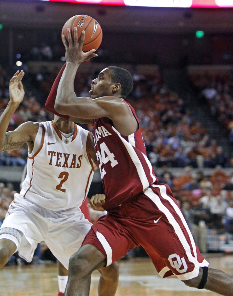 Oklahoma guard Buddy Hield (24) drives to the basket against Texas guard Demarcus Holland (2) during the second half of an NCAA college basketball game Saturday, Jan. 4, 2014, in Austin, Texas. Oklahoma won 88-85.  Hield led Oklahoma with 22 points. (AP Photo/Michael Thomas)