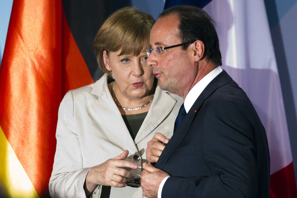 Photo -   FILE - In this May 15, 2012 file photo, German Chancellor Angela Merkel, left, talks to new French President Francois Hollande in Berlin. Merkel and Hollande said in a joint statement issued by the German government Friday, July 27, 2012 that their countries are