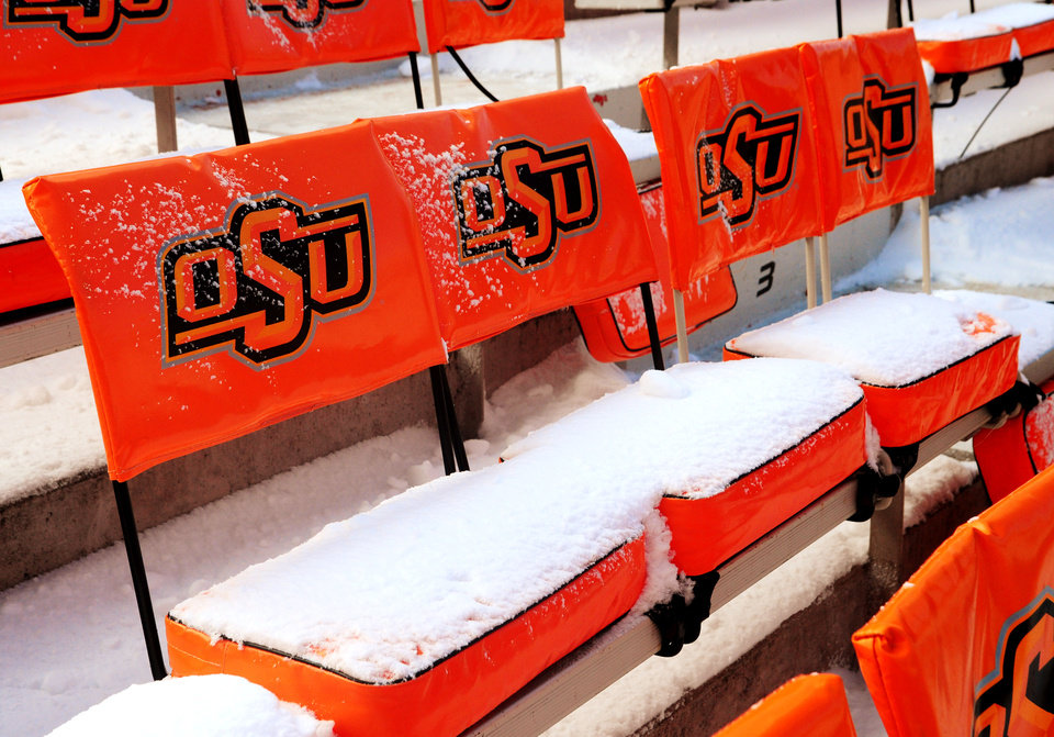 Snow piles up on chair backs inside Boone Pickens Stadium in Stillwater after the campus received heavy snowfall on Thursday and Friday ahead of Saturday's bedlam football game. The Oklahoma State athletic department was forced to clear the snow quickly, using small tractors to clear the field on Dec. 6, 2013. KT King/For the Tulsa World