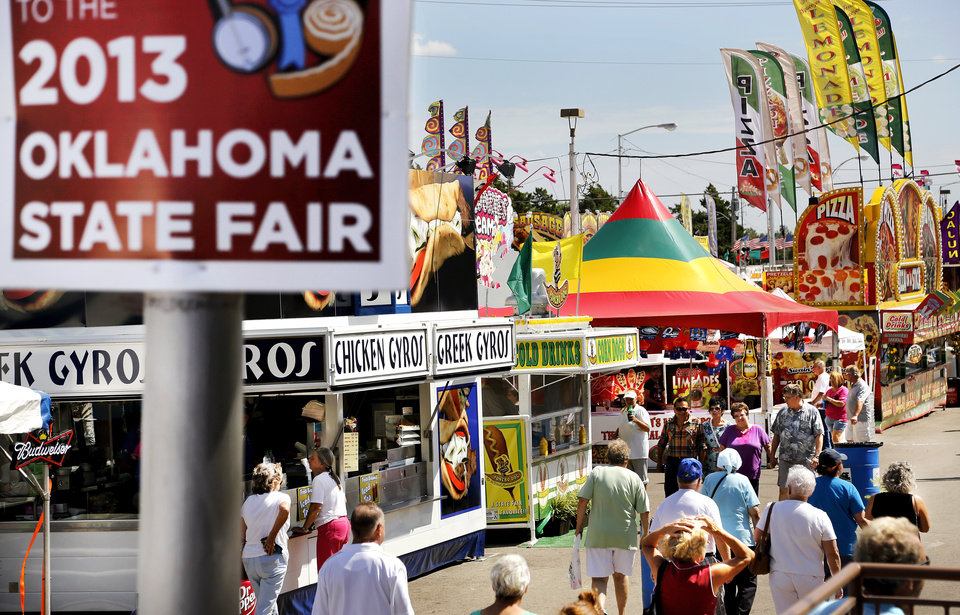 Photo - People walk past food vendors Wednesday, Sep. 18, 2013, at the Oklahoma State Fair.  Photo  by Jim Beckel, The Oklahoman.