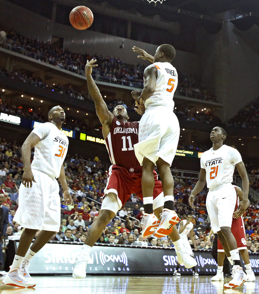 Photo - Oklahoma's Tommy Mason-Griffin (11) puts up a shot past Oklahoma State's Reger Dowell (5) in the first half of the college basketball game during the men's Big 12 Championship tournament at the Sprint Center on Wednesday, March 10, 2010, in Kansas City, Mo. Photo by Chris Landsberger, The Oklahoman