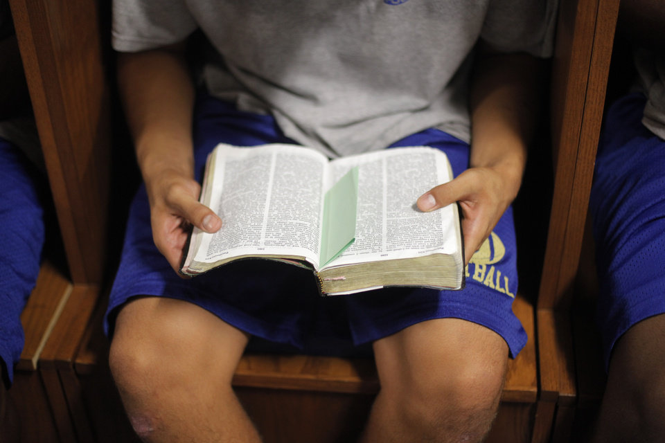 COLLEGE FOOTBALL: Westley Satoe, a freshman, reads his Bible in the locker room at Northeastern Oklahoma A&M College in Miami, Okla., Wednesday, July 18, 2012.  Photo by Garett Fisbeck, The Oklahoman