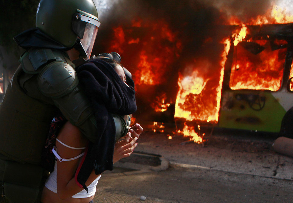 Photo -   A young woman is taken away by riot police as a public bus burns during clashes between students demanding free education and riot police in Santiago, Chile, Wednesday, Aug. 8, 2012. Police used water cannons and tear gas to break up the protest and three buses were set ablaze. (AP Photo/Luis Hidalgo)