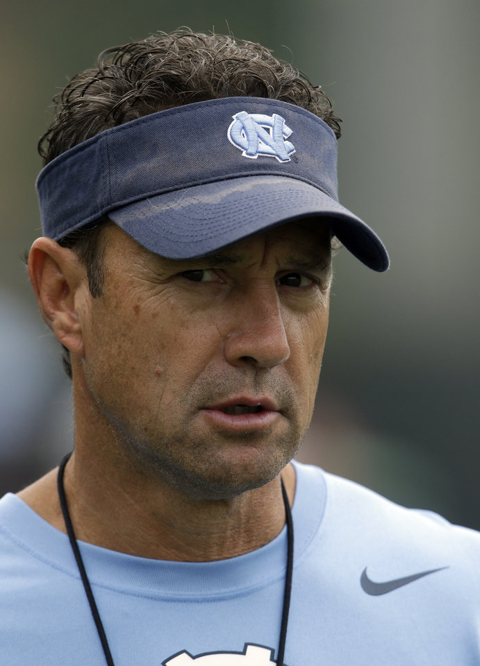 Photo - In this photo taken Friday, Aug. 1, 2014,  North Carolina coach Larry Fedora watches his team during an NCAA football practice in Chapel Hill, N.C. North Carolina has optimism from a strong finish and motivation from watching a rival's surprise run to the Atlantic Coast Conference championship game. (AP Photo/Gerry Broome)