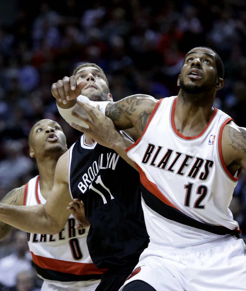 Photo - Brooklyn Nets center Brook Lopez (11) battles for position on a free throw rebound with the Portland Trail Blazers' LaMarcus Aldridge, right, and Damian Lillard during the first quarter of an NBA basketball game in Portland, Ore., Wednesday, March 27, 2013. (AP Photo/Don Ryan)