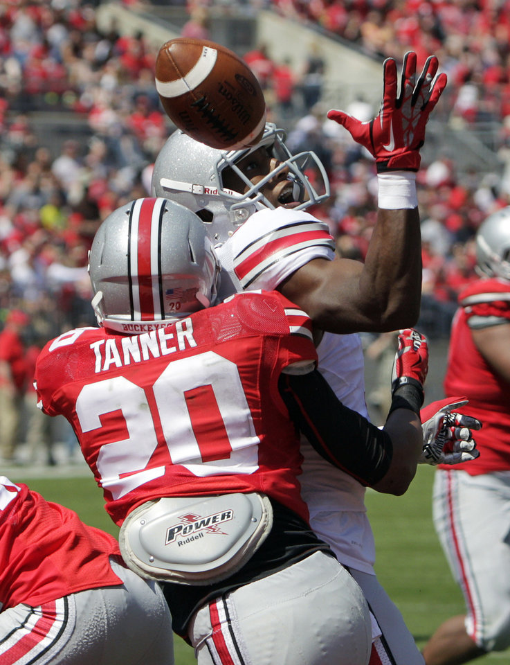 Photo - Ohio State wide receiver Michael Thomas, top, loses control of the ball as safety Ron Tanner defends during a spring NCAA college football game Saturday, April 12, 2014, in Columbus, Ohio. (AP Photo/Jay LaPrete)