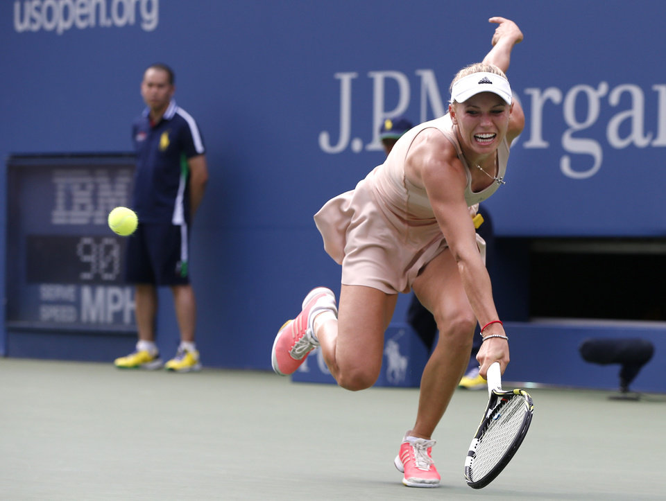 Photo - Caroline Wozniacki, of Denmark, returns a shot to Maria Sharapova, of Russia, during the fourth round of the 2014 U.S. Open tennis tournament, Sunday, Aug. 31, 2014, in New York. (AP Photo/Kathy Willens)