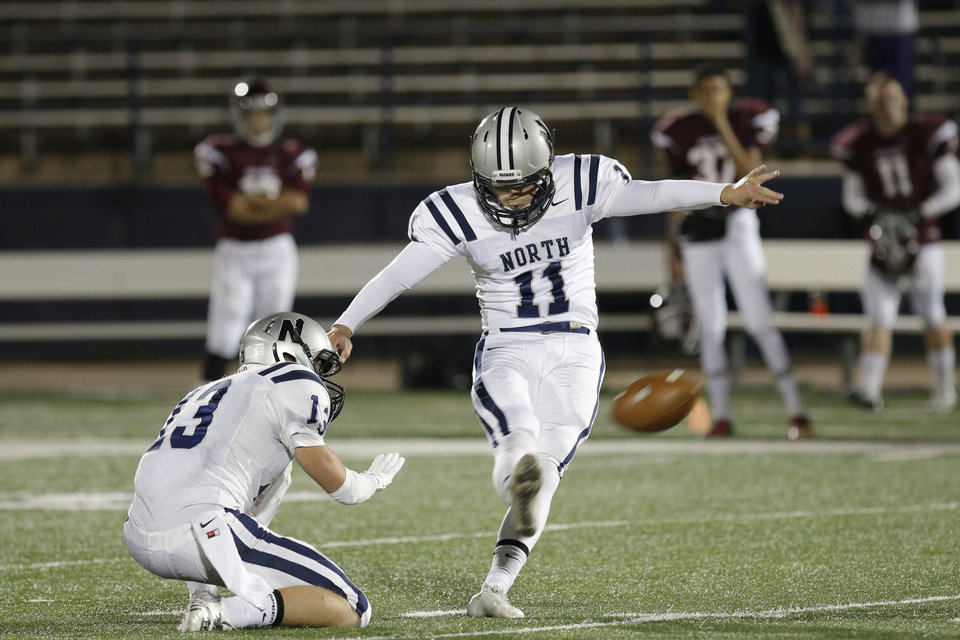 Photo - EN # 11 Trevor Moore makes his second field goal with #13 Kyle Willis holding during the high school football playoff game between Edmond North and Edmond Memorial at Watland Stadium in Edmond, Friday, November 15, 2013. Photo by Doug Hoke, The Oklahoman
