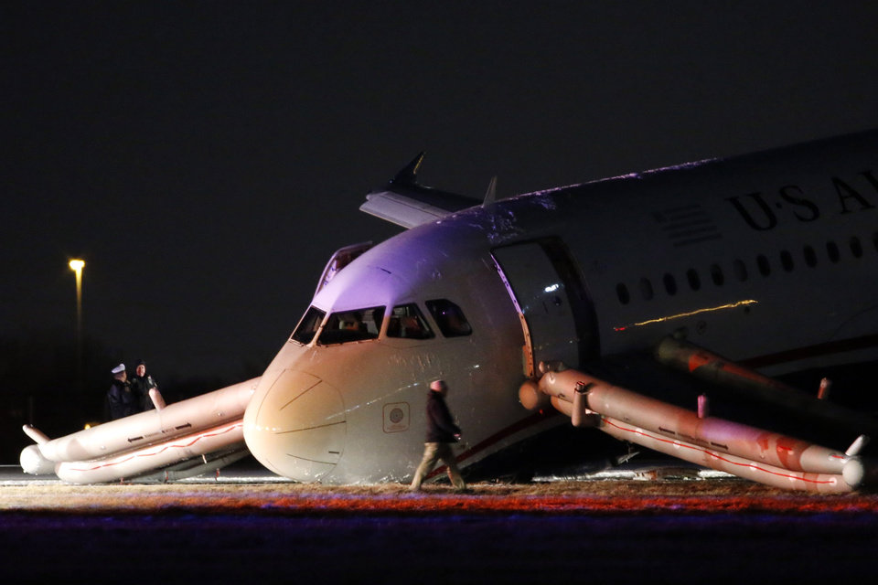 Photo - An investigator walks near a damaged US Airways jet at the end of a runway at the Philadelphia International Airport, Thursday, March 13, 2014, in Philadelphia. Airline officials said the flight was heading to Fort Lauderdale, Fla., when the pilot was forced to abort takeoff around 6:30 p.m., after the front landing gear failed. An airport spokeswoman said no injuries have been reported. (AP Photo/Matt Slocum)