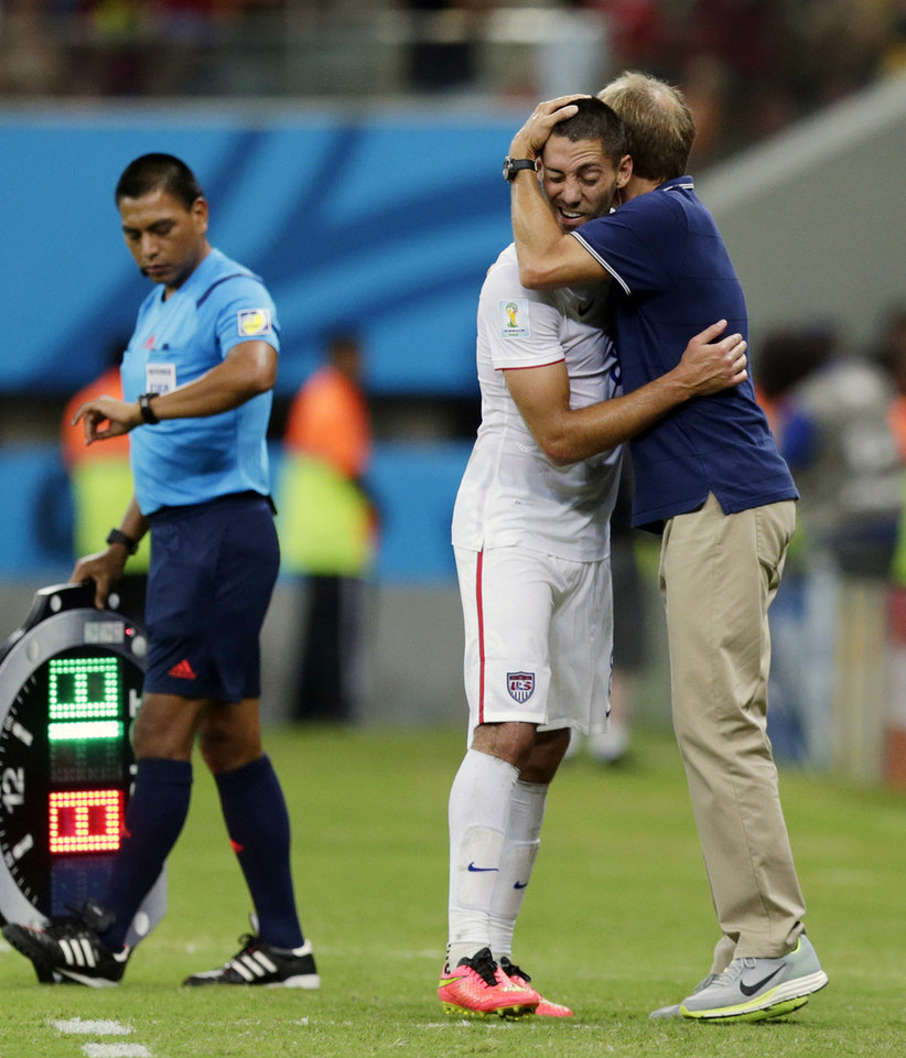 Photo - United States' head coach Juergen Klinsmann hugs United States' Clint Dempsey during the group G World Cup soccer match between the United States and Portugal at the Arena da Amazonia in Manaus, Brazil, Sunday, June 22, 2014. The United States and Portugal tied 2-2. (AP Photo/Julio Cortez)