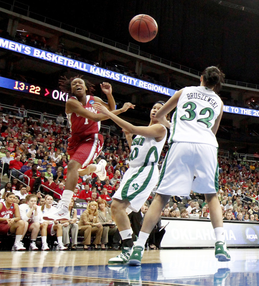 Photo - OU's Nyeshia Stevenson passes the ball over Notre Dame's Ashley Barlow, left, and Becca Bruszewski during the Sweet 16 round of the NCAA women's  basketball tournament in Kansas City, Mo., on Sunday, March 28, 2010. 