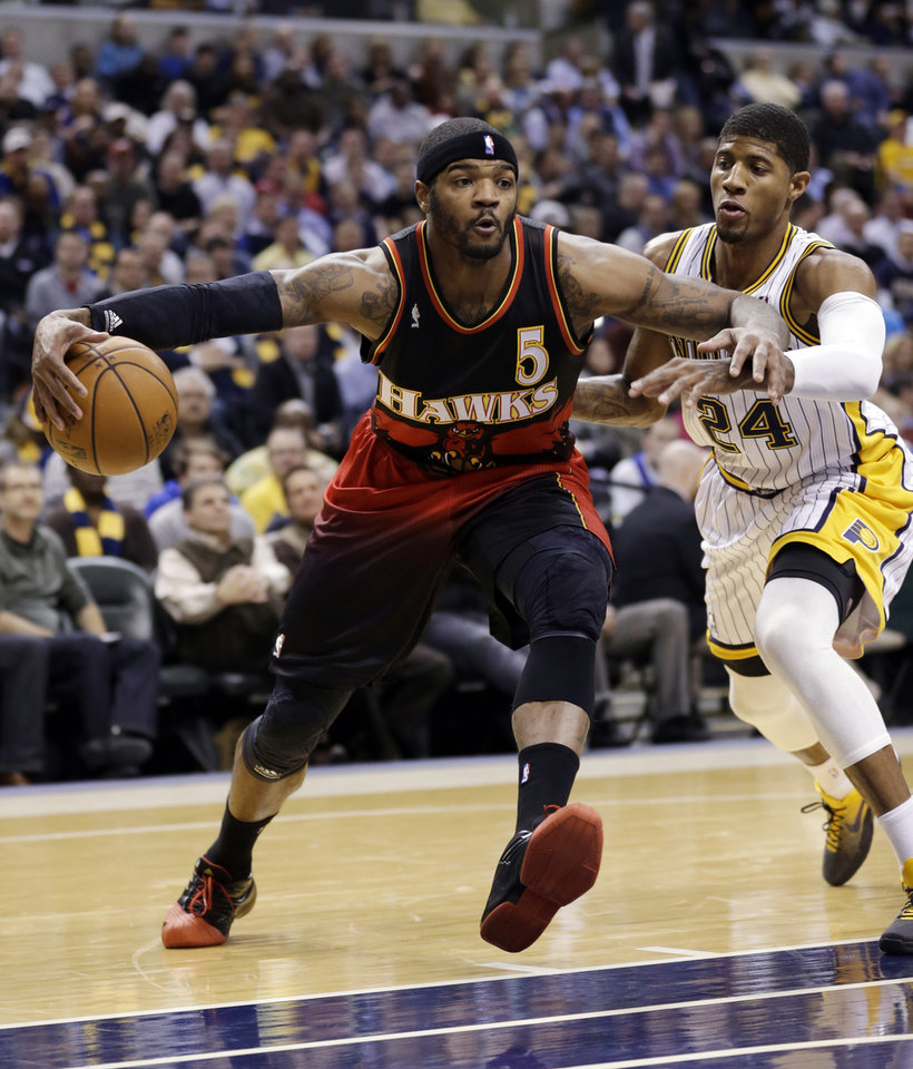 Atlanta Hawks forward Josh Smith, left, drives past Indiana Pacers forward Paul George during the first half of an NBA basketball game in Indianapolis, Tuesday, Feb. 5, 2013. (AP Photo/Michael Conroy)
