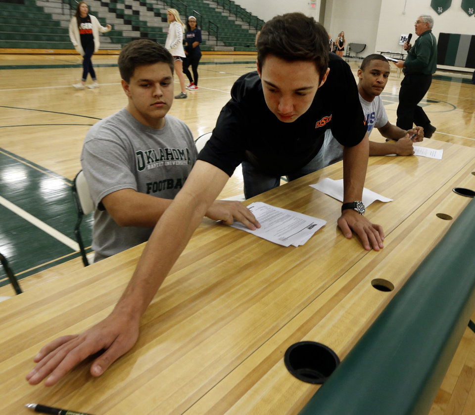 Photo - John Kolar reaches for a pen in front of teammate Trevor Magee at Norman North High School on Wednesday, Feb. 4, 2015  in Norman, Okla. Behind is Bo Garver.  Photo by Steve Sisney, The Oklahoman