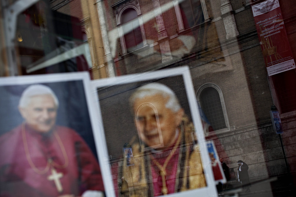 Photo - A nun is reflected in a shop window with portraits of Pope Benedict XVI, in Rome, Monday, Feb. 25, 2013. Pope Benedict XVI has changed the rules of the conclave that will elect his successor, allowing cardinals to move up the start date if all of them arrive in Rome before the usual 15-day transition between pontificates. Benedict signed a legal document, issued Monday, with some line-by-line changes to the 1996 Vatican law governing the election of a new pope. It is one of his last acts as pope before resigning Thursday. (AP Photo/Oded Balilty)