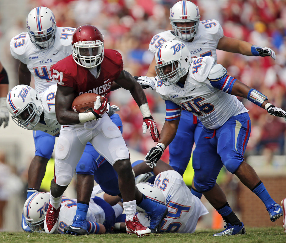 Oklahoma's Keith Ford (21) runs past the Tulsa defense during the college football game between the University of Oklahoma Sooners (OU) and the University of Tulsa Hurricanes (TU) at the Gaylord-Family Oklahoma Memorial Stadium on Saturday, Sept. 14, 2013 in Norman, Okla.  Photo by Chris Landsberger, The Oklahoman