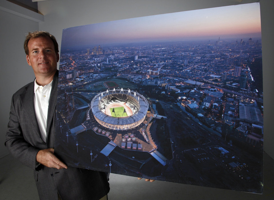 Photo - Todd Gralla, an architect with Populous in Norman, poses for a photo Monday. He is holding a photo of the Olympic Stadium in London that his company designed. Photo by Garett Fisbeck, The Oklahoman