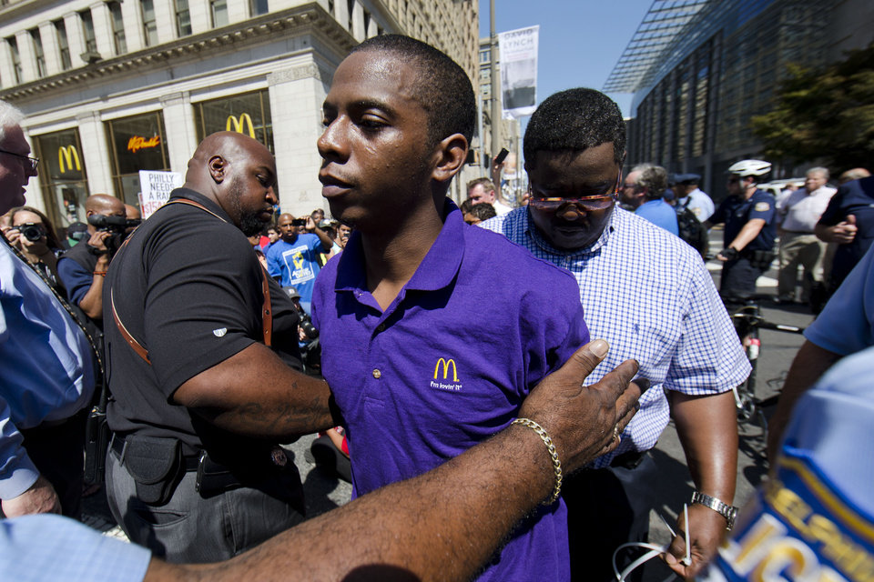 Photo - A McDonald's worker is detained by police during a protest to push fast-food chains to pay their employees at least $15 an hour, outside a McDonald's restaurant Thursday, Sept. 4, 2014, in Philadelphia. The protest movement, which is backed financially by the Service Employees International Union and others, has gained national attention at a time when the wage gap between the poor and the rich has become a hot political issue. (AP Photo/Matt Rourke)