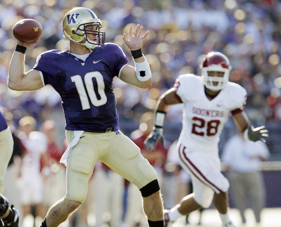 Photo - UW's Jake Locker (10) passes as OU's Travis Lewis (28) defends in the first half during the college football game between Oklahoma and Washington at Husky Stadium in Seattle, Wash., Saturday, September 13, 2008. BY NATE BILLINGS, THE OKLAHOMAN