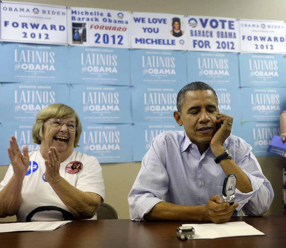 Photo -   President Barack Obama, right, calls supporters as campaign worker Ellen Merill, left, reacts at a local campaign office, Monday, Oct. 1, 2012 in Henderson, Nev. (AP Photo/Pablo Martinez Monsivais)