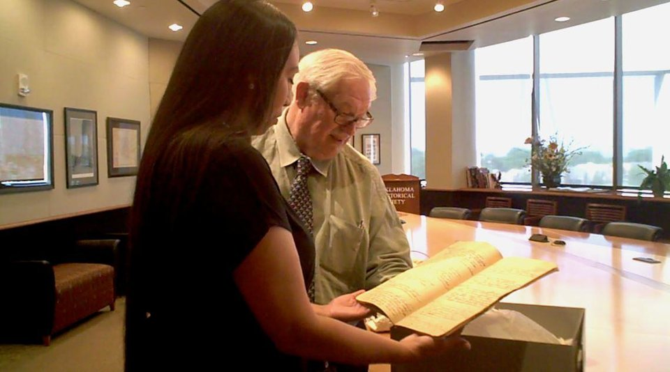 Photo -  At the Oklahoma History Center, Michelin Butler Lopez, of Altus, looks at handwritten journals that belonged to her great-great grandfather the Rev. David Pendleton Oakerhater, with William Welge, director of the center's office of American Indian culture and preservation. [Photo by Carla Hinton, The Oklahoman]