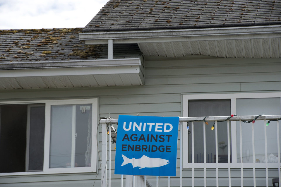 Photo - A sign against Enbridge hangs on a house in Kitimat, British Columbia, Tuesday, June 17, 2014. Canada's government on Tuesday approved a controversial pipeline proposal that would bring oil to the Pacific Coast for shipment to Asia, a major step in the country's efforts to diversify its oil exports if it can overcome fierce opposition from environmental and aboriginal groups. Approval for Enbridge's Northern Gateway project was expected as Canada needs infrastructure in place to export its growing oil sands production. (AP Photo/The Canadian Press, Jonathan Hayward)