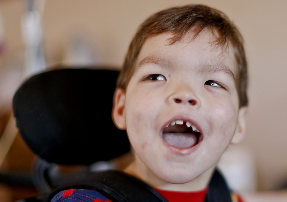 Photo - Ashley Zeno's son Joey laughs while sitting in his wheel chair at his home on Monday, March 4, 2013, in Mustang, Okla. Joey has Cri du Chat syndrome which is a condition that is similar to autism, but requires around the clock medical supervision. Zeno, a single mom, is a nurse as well as Joey's in home nurse. Recent proposals by The Oklahoma Health Care Authority want to eliminate the ability of family members serving as in-home nurses, and being reimbursed for the care they provide. For Zeno, this means she would need to find two dependable in-home nurses, and a job outside the home that would let her take off for the multiple doctor appointments Joey requires each week.Photo by Chris Landsberger, The Oklahoman