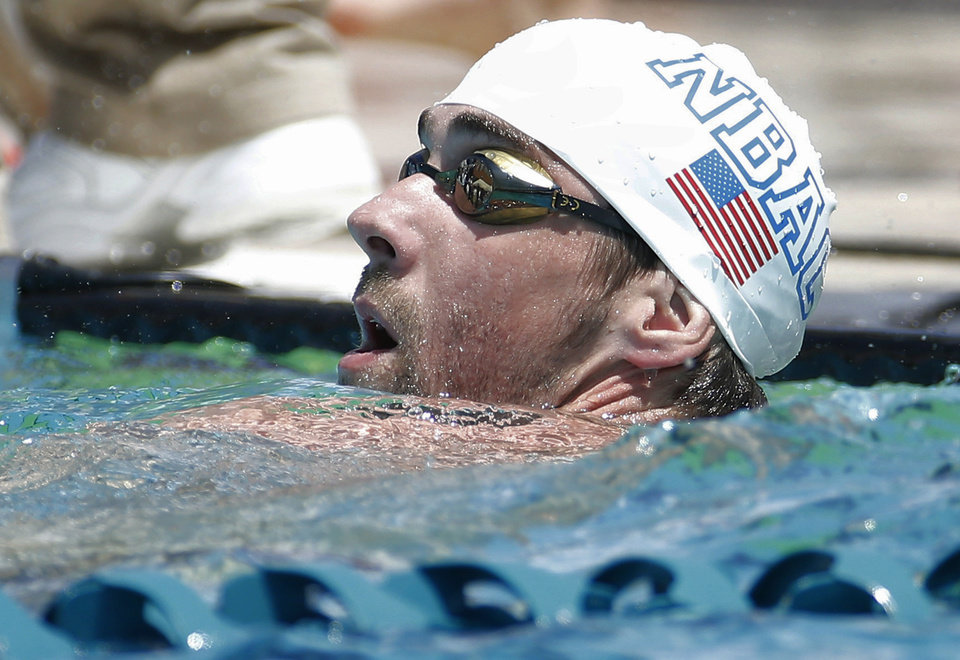 Photo - Michael Phelps looks at the scoreboard after the 100-meter butterfly during the Arena Grand Prix swim meet, Thursday, April 24, 2014, in Mesa, Ariz. It is Phelps' first competitive event after a nearly two-year retirement. (AP Photo/Matt York)