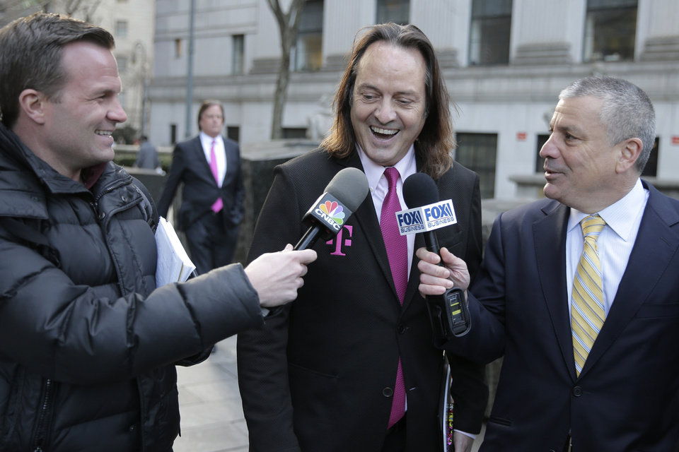 Photo -  T-Mobile chief executive John Legere speaks to reporters Jan. 15 as he leaves the courthouse in New York. A federal judge has removed a major obstacle to T-Mobile's $26.5 billion takeover of Sprint, as he rejected claims by a group of states that the deal would mean less competition and higher phone bills. [Seth Wenig/Associated Press file photo]