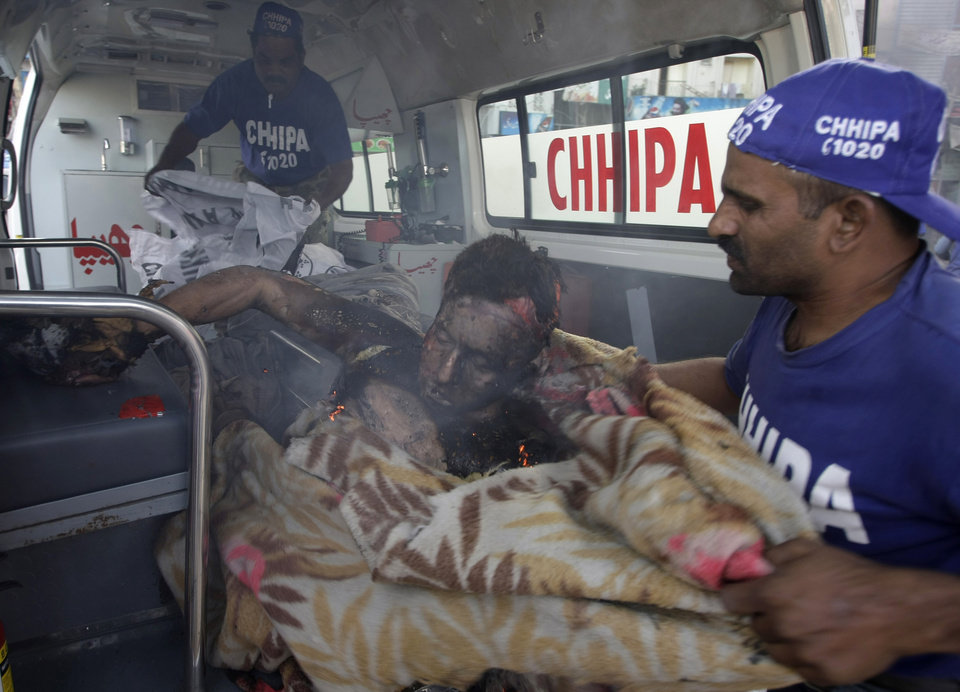 EDS NOTE: GRAPHIC CONTENT - Pakistani volunteers help a critically injured passenger on his way to a hospital following a blast in Karachi, Pakistan on Saturday, Dec. 29, 2012. The blast that ripped through the bus  set the vehicle on fire and reduced it to little more than a charred skeleton, killing scores of people and left many injured. Police were trying to determine whether the explosion was caused by a bomb or a gas cylinder, said police spokesman. Many buses in Pakistan run on natural gas. (AP Photo/Fareed Khan)