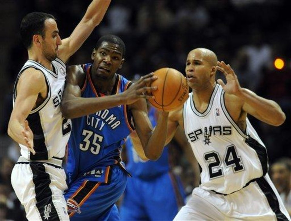 Photo - Oklahoma City Thunder guard Kevin Durant (35) looks to pass from a double-team of San Antonio Spurs' Manu Ginobili, left, of Argentina, and Richard Jefferson during the second half of an NBA basketball game at the AT&T Center in San Antonio, Wednesday, Feb. 24, 2010. Durant's streak of 29 games with at least 25 points came to an end as the Spurs defeated the Thunder 95-87.(AP Photo/ Bahram Mark Sobhani)