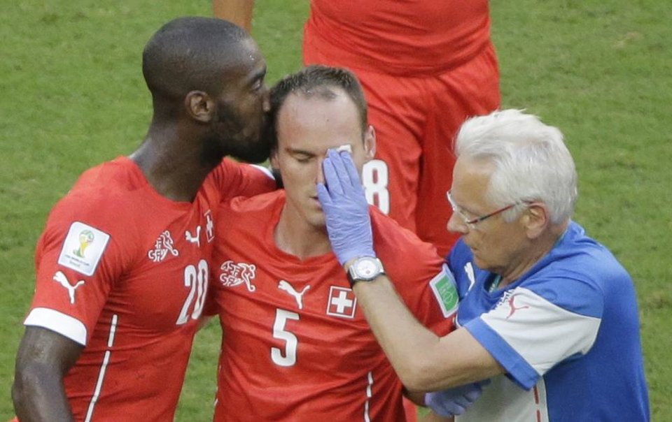 Photo - Switzerland's Johan Djourou, left, kisses his injured teammate Steve von Bergen during the group E World Cup soccer match between Switzerland and France at the Arena Fonte Nova in Salvador, Brazil, Friday, June 20, 2014. (AP Photo/Sergei Grits)